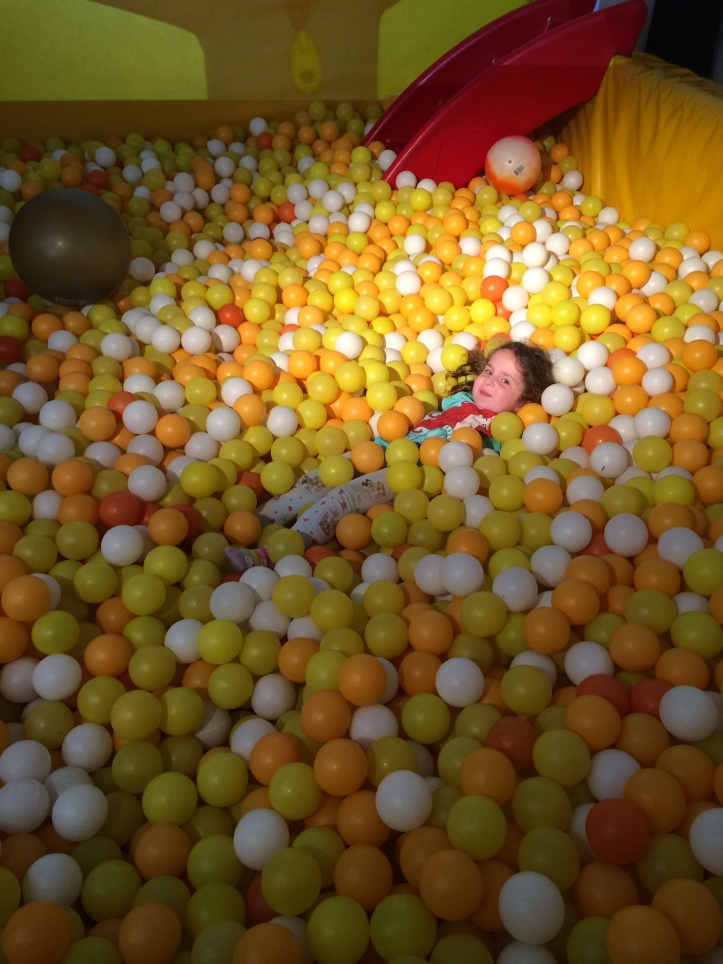 Little girl in a ball pit